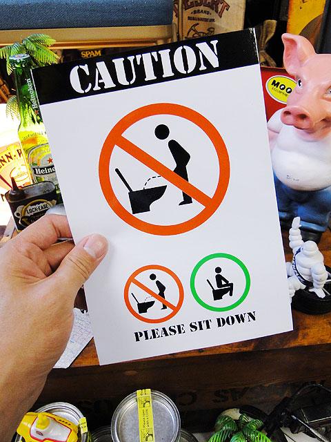 「トイレは座ってしてください」の警告ステッカー
