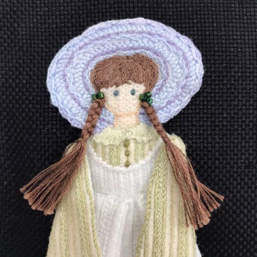 エプロンドレスの少女の額(黄色い帽子・緑のドレス)