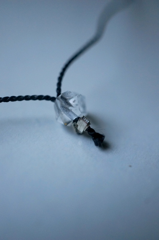 in her Clear stone silk necklace