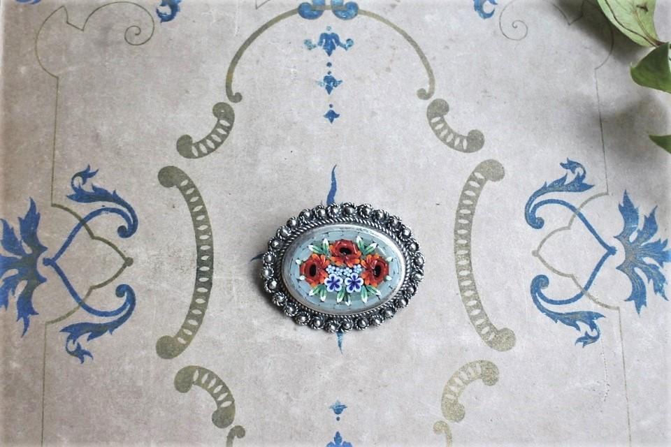 イタリア製 淡いブルーに鮮やかな赤い花とブルーの花が嵌め込まれたブーケ柄のマイクロモザイクブローチ 509501
