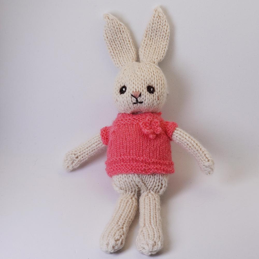 高級カシミヤの棒針の編みぐるみ。コサージュが付いたピンクのセーターを着たブラブラ・ポーラーうさぎ【20cm】