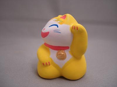 西に黄色の金運猫 (わはは 左手上げ)
